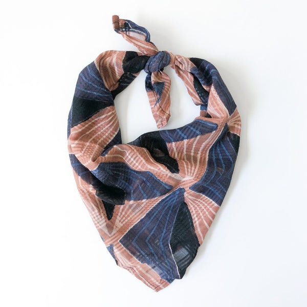A blue and pink bandana, folded over and tied in a knot. Block printed by hand, the Lola Bandana from Maelu is designed in Portland, Oregon and handmade in India.