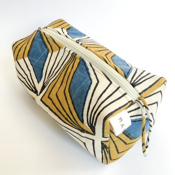 A yellow, cream and blue patterned cosmetic bag. The Hattie Cosmetic Bag from Maelu is designed in Portland, Oregon and printed and made in India.