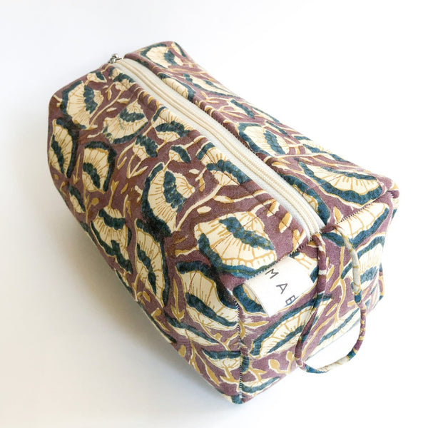 A brown, cream and dark blue floral patterned cosmetic bag. The Lena Cosmetic Bag from Maelu is designed in Portland, Oregon and printed and made in India.