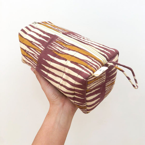 A person holding a maroon, mustard and cream patterned cosmetic bag. The Paloma Cosmetic Bag from Maelu is designed in Portland, Oregon and printed and made in India.