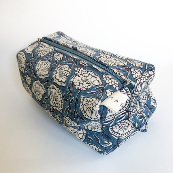 A blue and cream floral patterned cosmetic bag. The Poppy Cosmetic Bag from Maelu is designed in Portland, Oregon and printed and made in India.