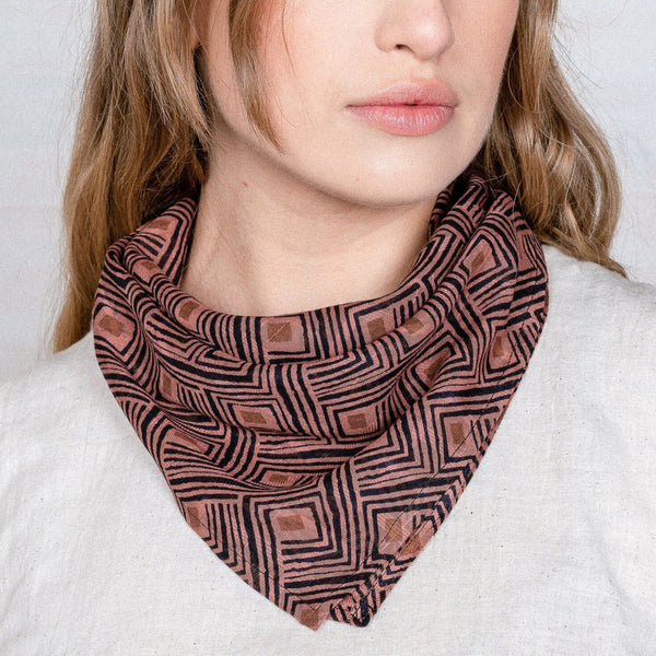 A woman wears a pink printed bandana around her neck. The Rumi Bandana from Maelu is designed in Portland, Oregon and made and printed by hand in India.