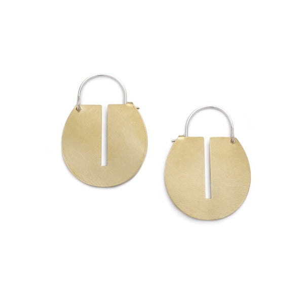 Small, round, brushed brass disc hoop earrings with a thin, rectangular cutout running down the center of the discs, and short, sterling silver earring wires that latch to the back of the discs. Hand-crafted in Portland, Oregon.