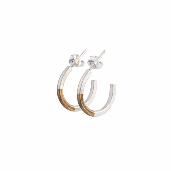 Minimalist and lightweight miniature hoop earrings of mixed brass and sterling silver hand-forged wire, with soldered sterling silver earring posts and sterling silver butterfly backings. Hand-crafted in Portland, Oregon.