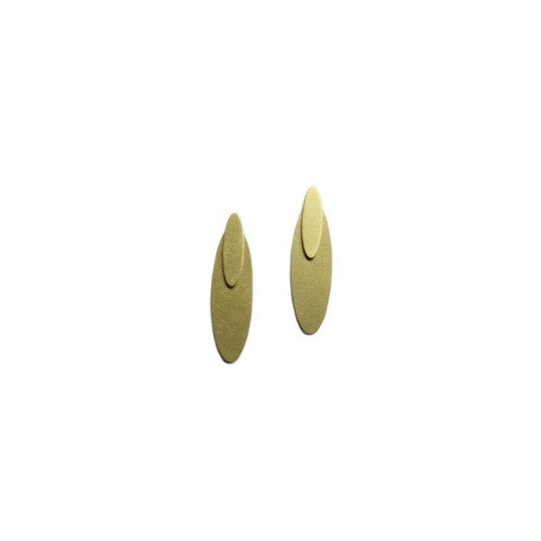A pair of oval brass earrings against a white background. The Oval Ear Jacket earrings are from Portland designer Natalie Joy.