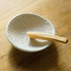 A white embossed offering bowl holding a stick of Palo Santo. Handmade by ceramicist Ellen Hammen.