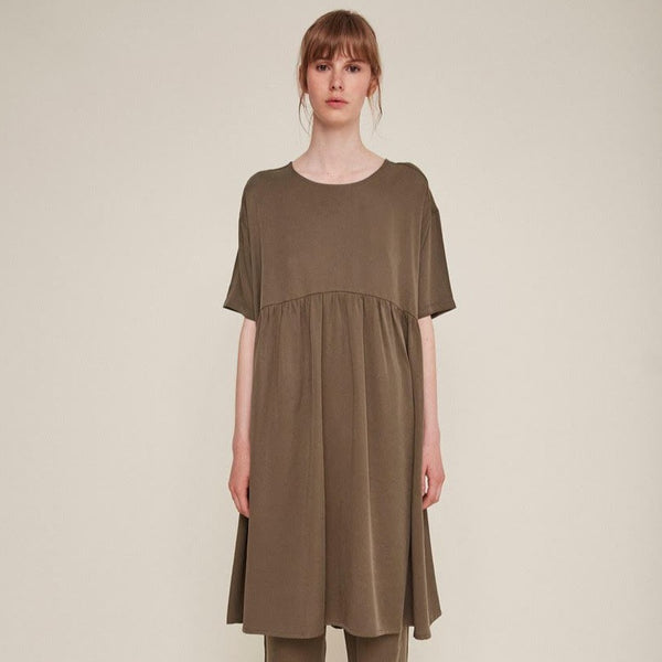 Red-haired woman wears a brown babydoll dress and matching pants. The Drapey Dress in Kaki is from designer Rita Row.