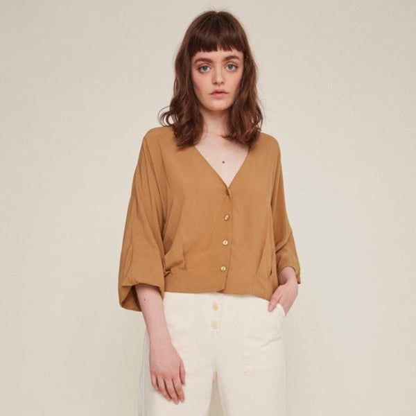 Red-haired woman wears a brown button-down blouse with loose sleeves and white pants. The Rosetta Blouse in Latte is from designer Rita Row.