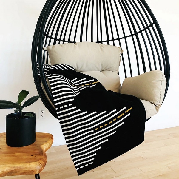 Black blanket with a white and gold striped pattern lays draped in a hanging chair. The Reika Throw blanket from Seek and Swoon is designed in Portland, Oregon and made in USA.