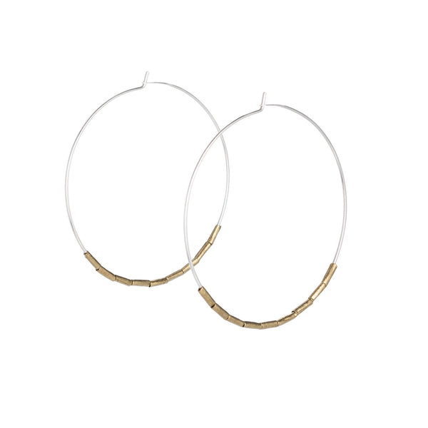 Lightweight, thin, sterling silver statement hoop earrings, accented with small, brass, African trade beads. Hand-formed in Portland, Oregon.