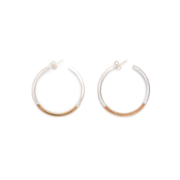 Small, minimalist, and lightweight hoop earrings of mixed brass and sterling silver hand-forged wire, with soldered sterling silver earring posts and sterling silver butterfly backings. Hand-crafted in Portland, Oregon.