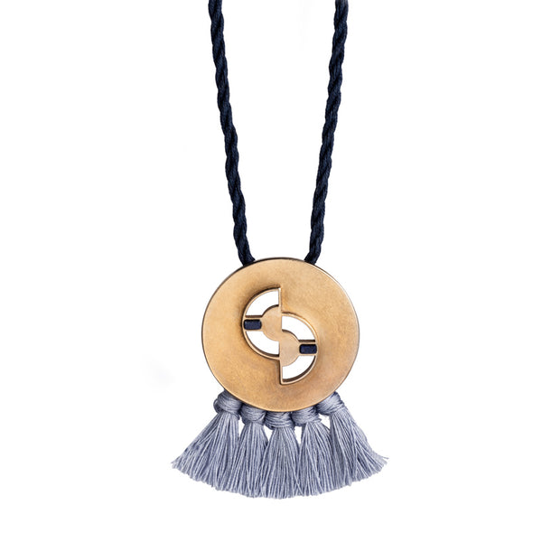 Circular, quarter-sized, cast-bronze pendant with curved cutouts, two rectangular, lapis lazuli inlays, and periwinkle cotton fringe, threaded with a navy blue cotton rope. Hand-crafted in Portland, Oregon.