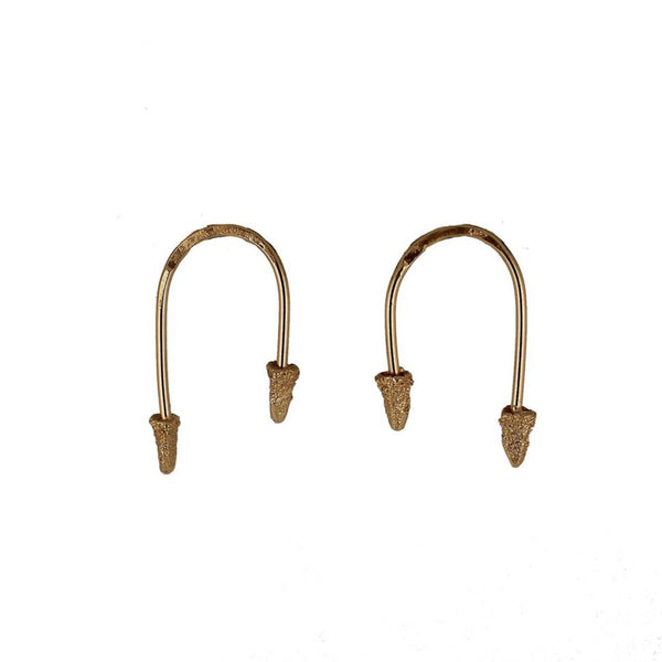"""U"" shaped brass wire earrings with brass cones on each end. The brass cones are cast in cuttlefish bones. The Which Way to Go earrings are made by designer Lingua Nigra."