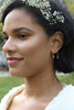 "Woman wears white flowers in her hair and models ""U"" shaped brass earrings. The Which Way to Go Earrings are made by designer Lingua Nigra."