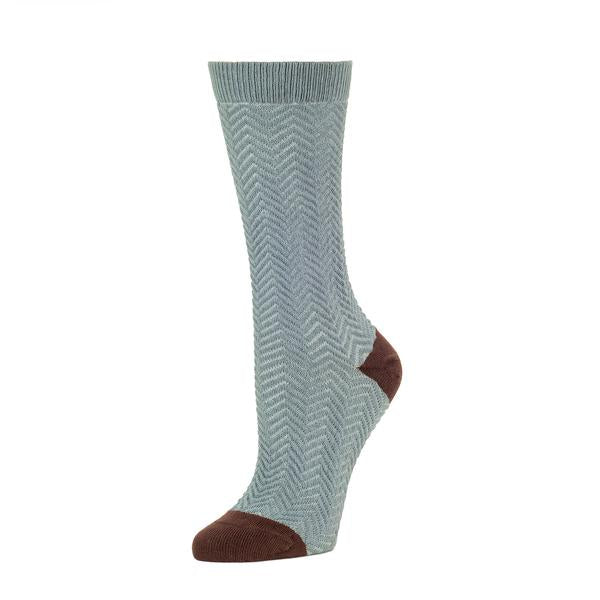 A grey-blue sock with a herringbone pattern stands against a white background. The heel and toe of the sock are brown. The Chunky Knit Herringbone Crew Sock in Lead is from Zkano, and made in Alabama, USA.