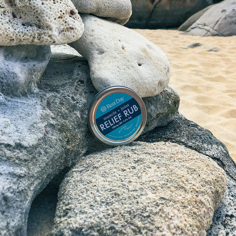 Muscle and Joint Relief Rub on rocks at the beach