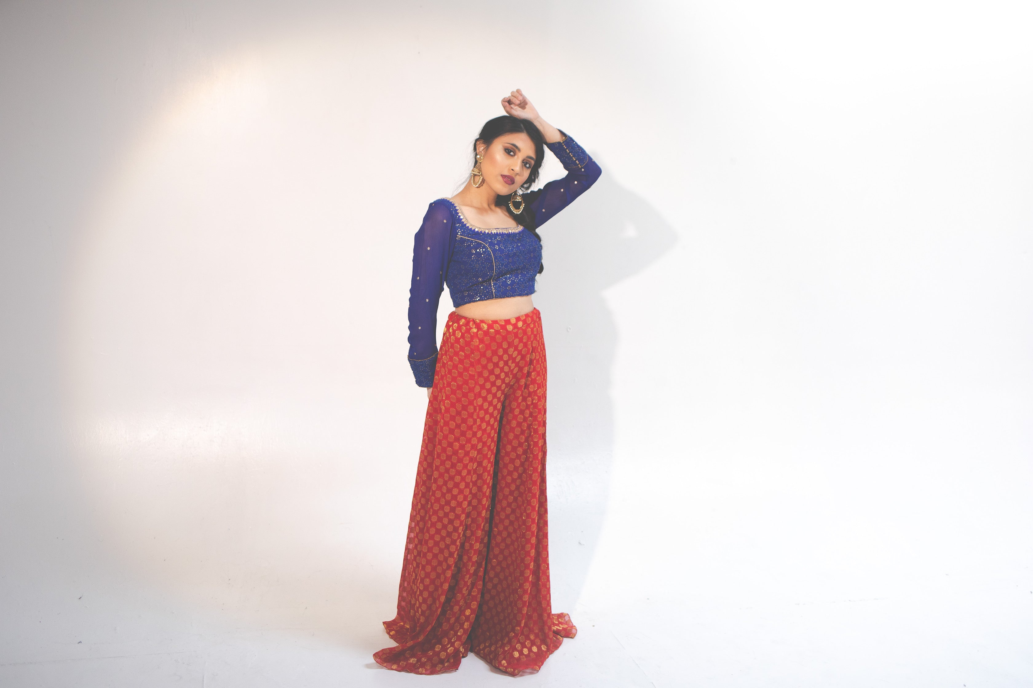 Model wearing Front blue silk long sleeved blouse with shimmering gold and mirrors and red silk pants