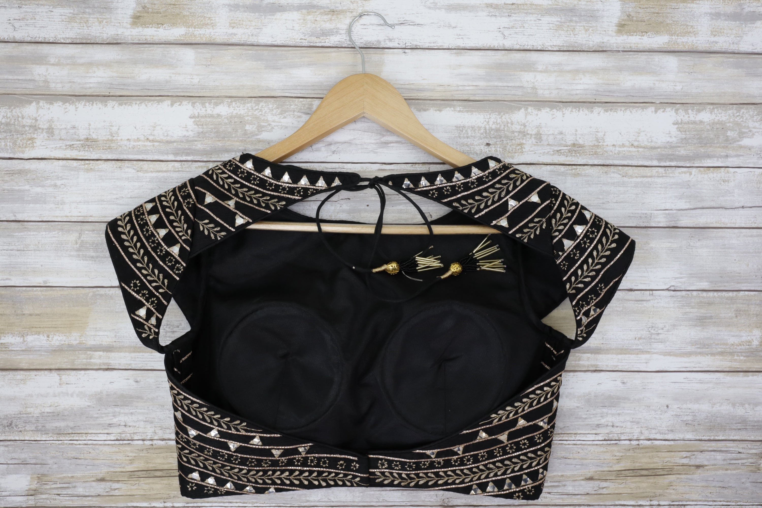 Black and gold blouse rental that features an open back, gold embroidery and shimmering mirror work.