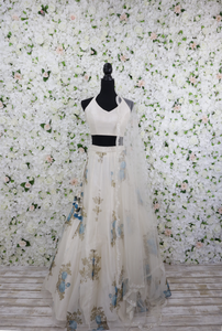 White and blue floral lehenga skirt with a matching blouse and dupatta