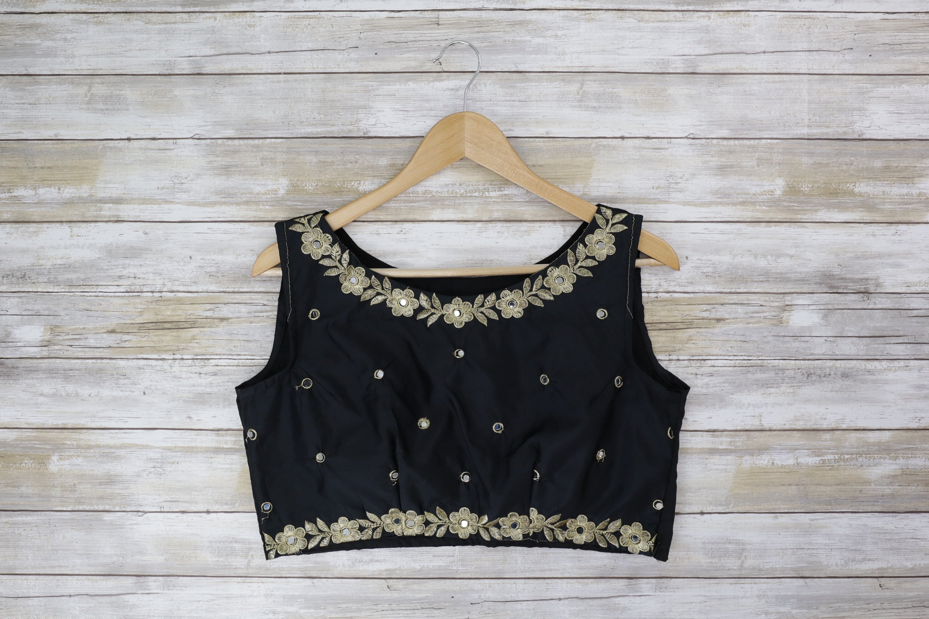 Black and gold sleeveless blouse with glimmering embroidery