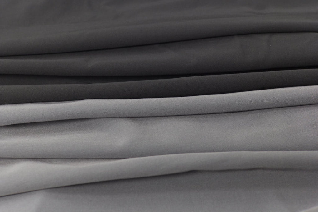 Stacks of Black Finch 4 way stretch, antimicrobial, moisture wicking, wrinkle resistant woven fabric in black and gray with a triblend of polyester, rayon, and spandex.