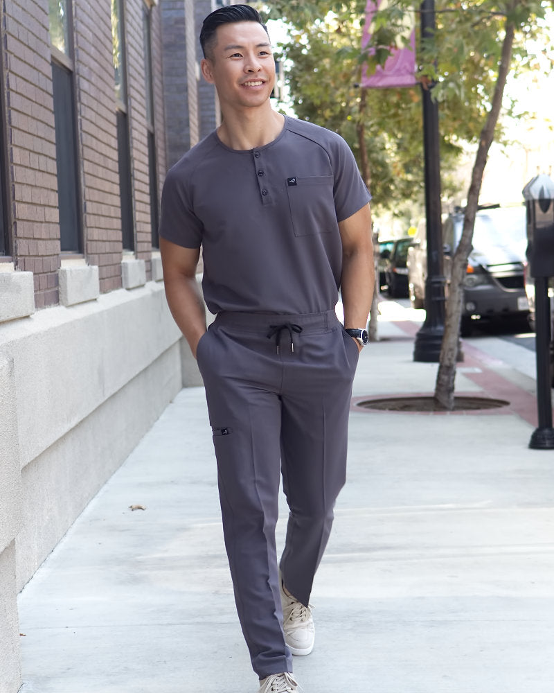 Black Finch Scrubs, Impact top.  Slim fit Henley men's scrub shirt in gray, lifestyle view.