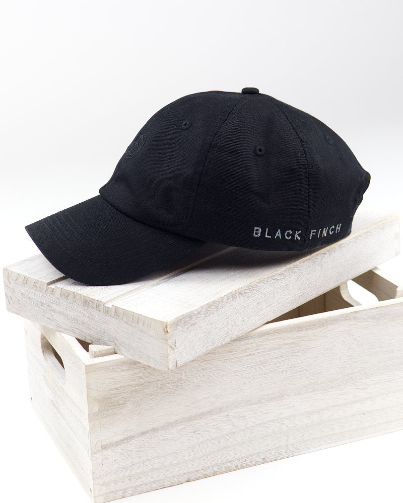 Black Finch Midnight Unisex Dad Hat in black side view on white crate.