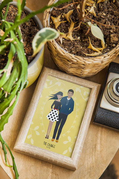 A whimsical stylized cartoon family portrait art print of Asian couple in a small frame lying on desk