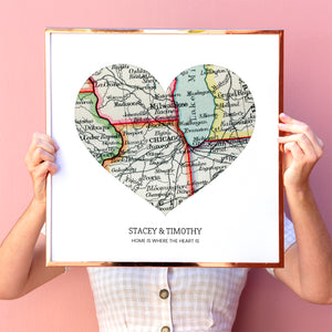 Woman holding up personalized heart shaped vintage map art print. The heart contains one map. Custom text on the map reads Stacy & Timothy.