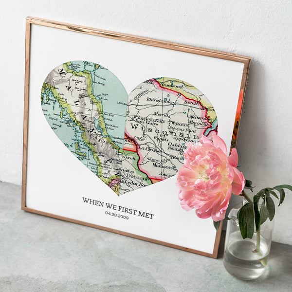 Personalized heart shaped vintage map art print leaning up against the wall. The print shows two maps side by side. A flower appears next to map as decoration.