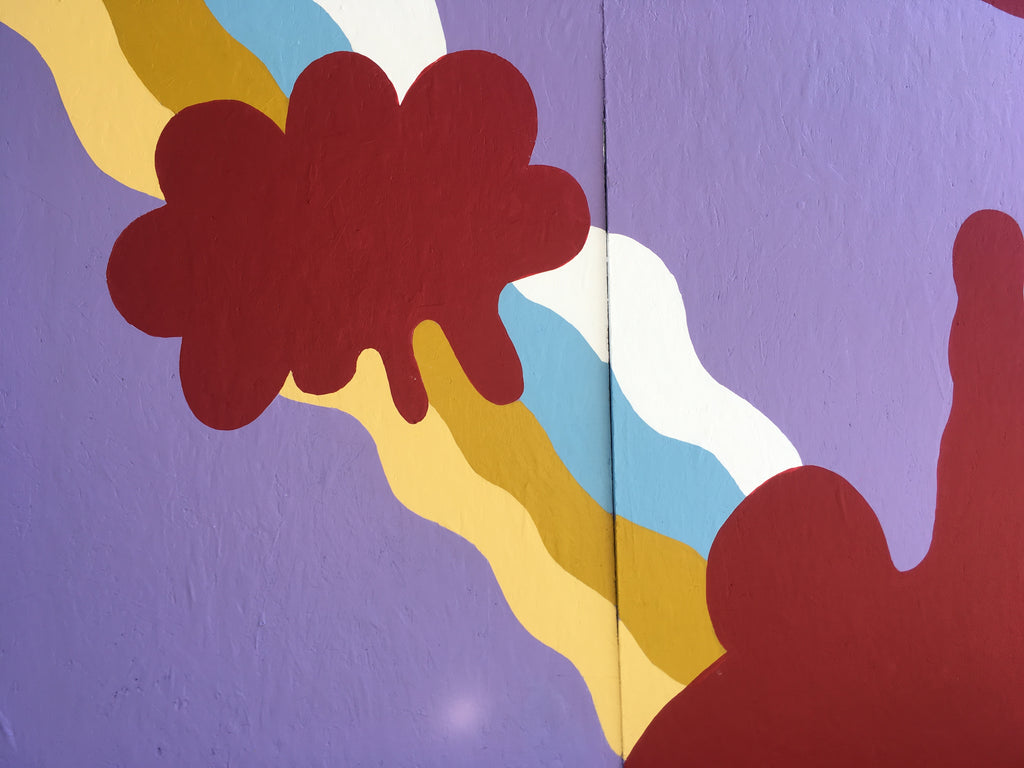 Close up mural of cloud shapes with a rainbow background. Mural artist in Capitol Hill
