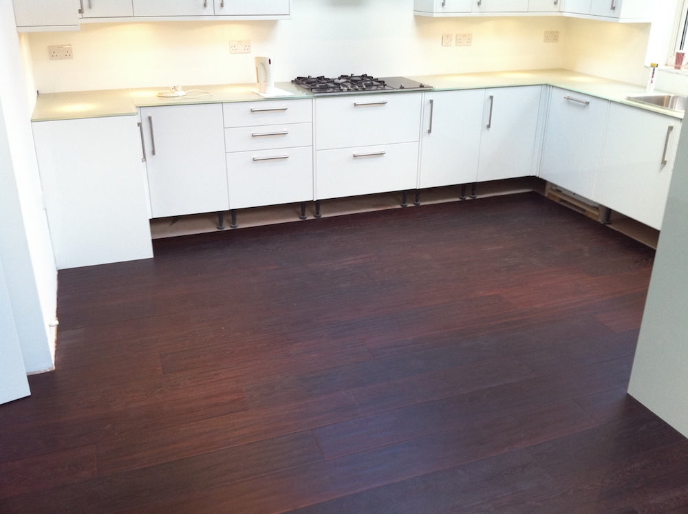 modern kitchen fitted with dark wood flooring