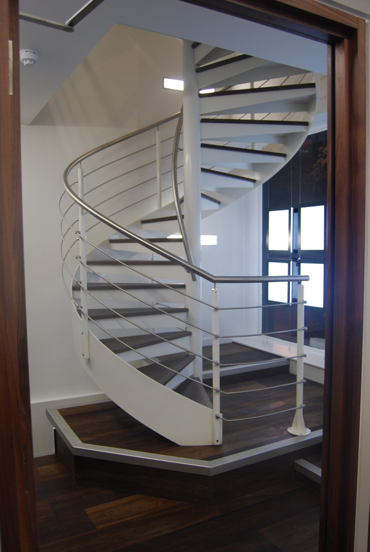 Spiral Staircase clad with double brushed fumed oak with contrasting metal edges