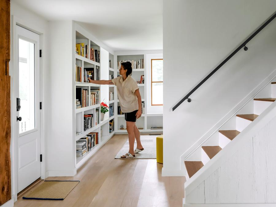 An interior space, a bookshelf with books and a staircase, a person pulling a book from the bookshelf