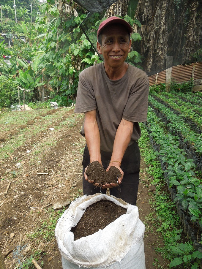 Farmer shows off healthy compost to fertilize nursery seedlings