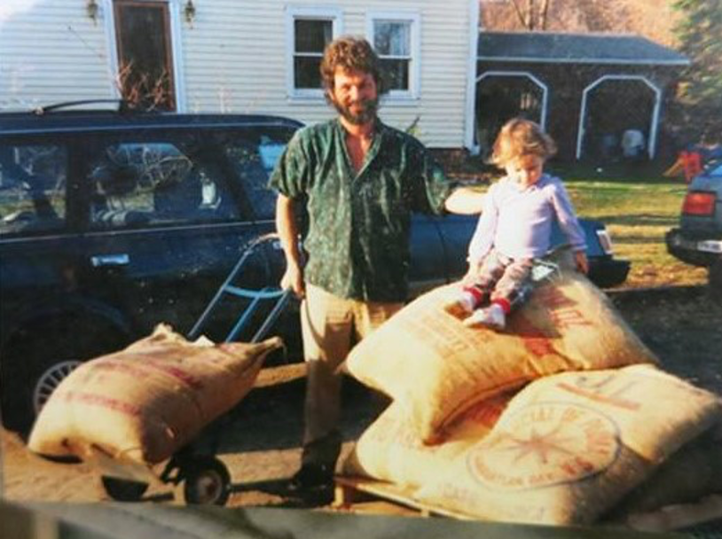 Dean with daughter sitting on coffee bags