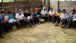 Cooperative members having a meeting in a dirt floored room