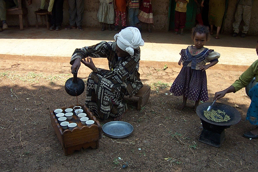 Ethiopian women roasting and pouring coffee; a young girl looks on