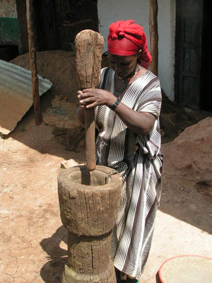 Ethiopian woman using a large mortar and pestle