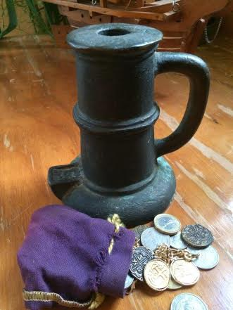 A thunder mug and a small, purple bag with pirates booty spilling out