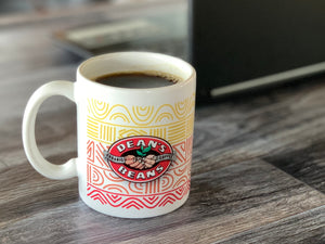 White ceramic coffee mug with colorful patterns and Dean's Beans logo