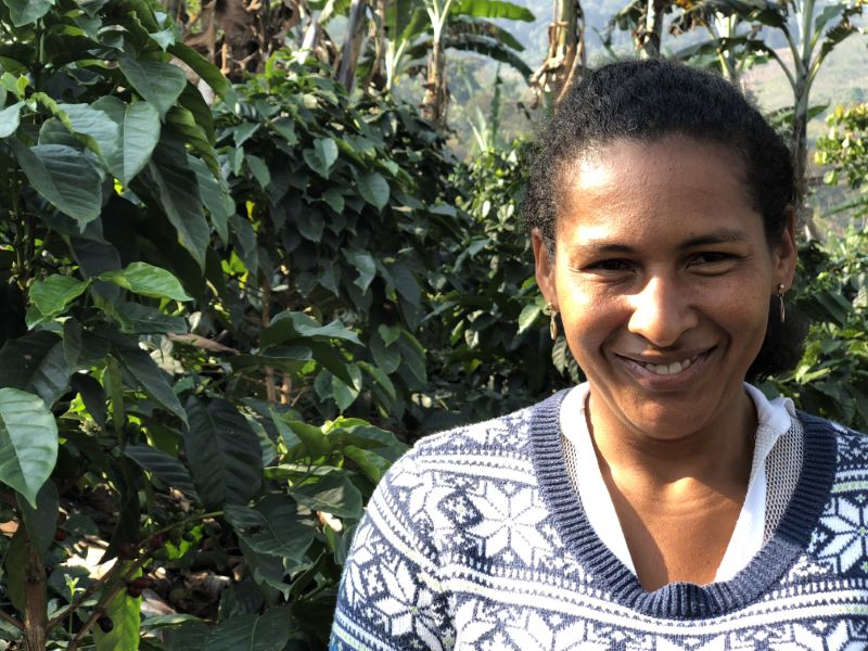 A Colombian woman smiling in front of coffee plants