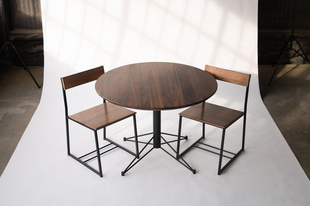 small round dining table with wood top and metal base  by Edgework Creative