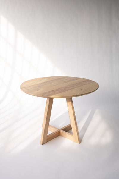 Round wood dining table by Edgework Creative