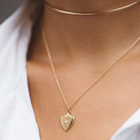 gold pendant, gold necklace, gold necklace and white collared shir, gold necklace on chest