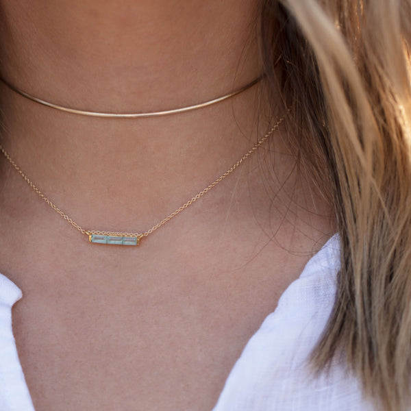 Channel aqua necklace, gold necklace, blonde hair, layered necklaces, white top