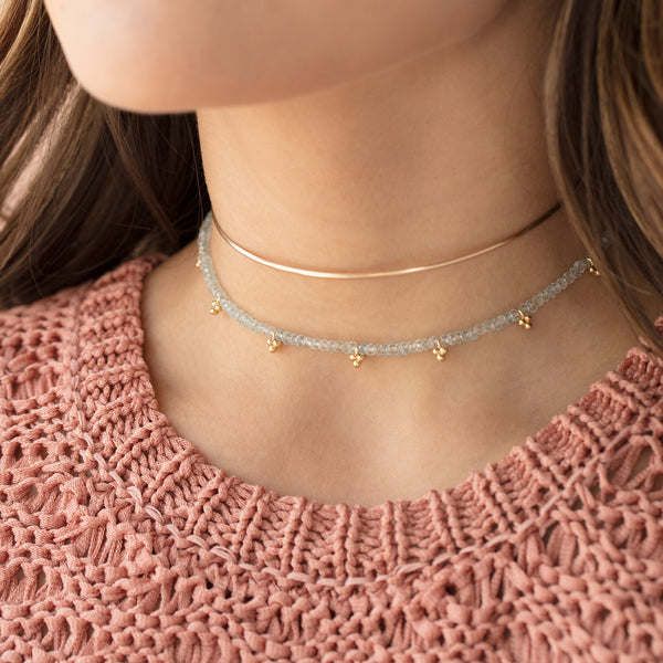 Fluency aquamarine gold choker, layered necklaces, pink knit sweater, brown hair