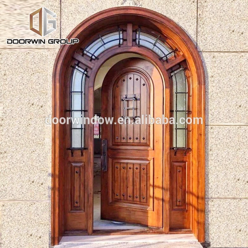 Arched top iron clavos door design with Q-Lon weather strip insulation and solid wood front door frame by Doorwin