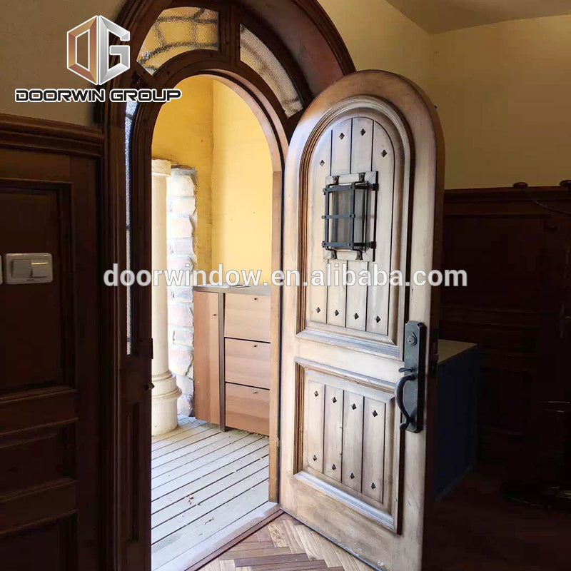 Church gate style design exterior wood front doors with top carving glass entry door with side lite rustic door by Doorwin