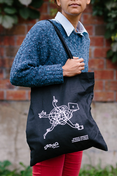 Person holding S'ATTAQ tote bag